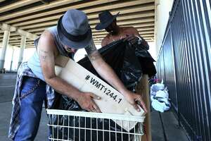 Edwin Ford, right, and Roy Dailey are packing up their belongings into a small cart in preparation for moving from underneath the overpass of U.S. 59 at Congress Ave. Friday.