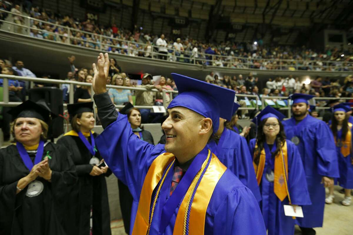 Cesar Mendez, 29, waves to family during the Friday's graduation ceremony.