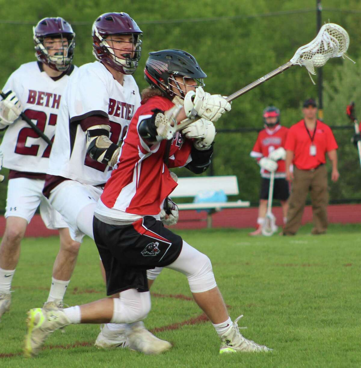 Pomperaug's Evan Cyganowski, right, looks for an opening as Bethel's Luke Newman, center, and Aiden Vizi defend during the boys lacrosse game at Bethel High School May 12, 2017.