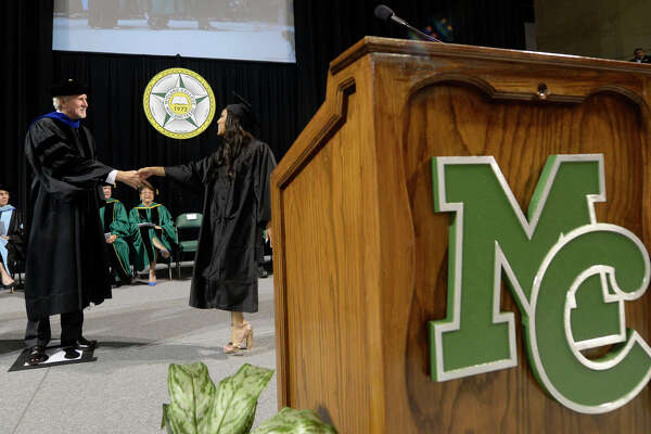 Tae'lor Hodge is congratulated by Midland College president Dr. Steve Thomas while walking the stage during the Midland College commencement ceremony May 12, 2017, at Chaparral Center.  James Durbin/Reporter-Telegram