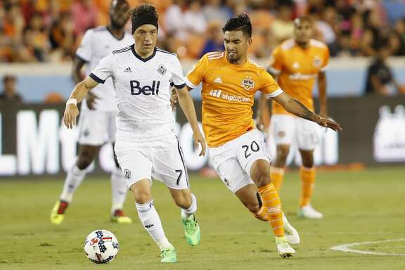 Vancouver Whitecaps midfielder Christian Bolanos (7) controls the ball defended by Houston Dynamo defender A. J. DeLaGarza (20) in the first half during the MLS game between the Houston Dynamo and the Vancouver Whitecaps at BBVA Compass Stadium on Friday, May 12, 2017, in Houston, TX.