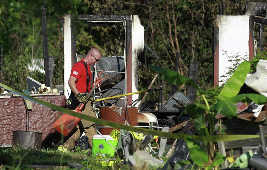 A fire fighter with The Woodlands Fire Department works the scene of a two-story house fire that left three people dead on Johnson Road, Friday, May 12, 2017, in Conroe. Photo: Jason Fochtman, Staff Photographer / Conroe Courier / HCN