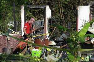 A fire fighter with The Woodlands Fire Department works the scene of a two-story house fire that left three people dead on Johnson Road, Friday, May 12, 2017, in Conroe.