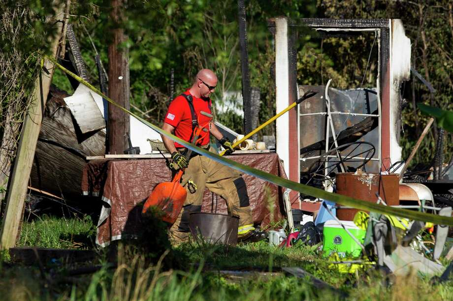 A fire fighter from The Woodlands Fire Department helps clean up debris from the scene of a house fire that killed three children between the ages of 6 and 13 on Johnson Road, Friday, May 12, 2017, in the community of Tamina, just east of The Woodlands. Five family members - a grandfather, grandmother, their son, their daughter, who was a mother of the three deceased children, and her fourth child, age 10  - were injured. Photo: Jason Fochtman, Staff Photographer / © 2017 Houston Chronicle