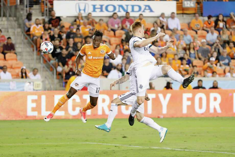 Dynamo forward Alberth Elis (17) scores past two Vancouver Whitecaps defenders during the first half at BBVA Compass Stadium. Photo: Tim Warner, Freelance / Houston Chronicle