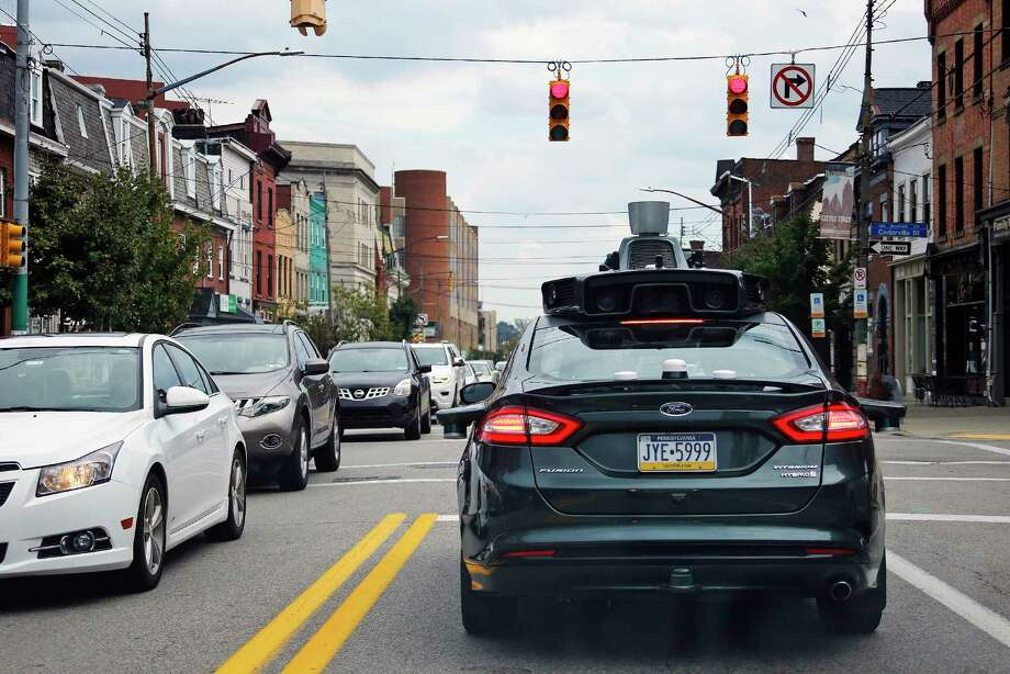 "A self-driving Uber car stops at a red light in Pittsburgh. ""There's an endless list of these cases where we as humans know the context, we know when to bend the rules and when to break the rules,"" says a computer engineering professor. Photo: Gene J. Puskar, STF / Copyright 2016 The Associated Press. All rights reserved."