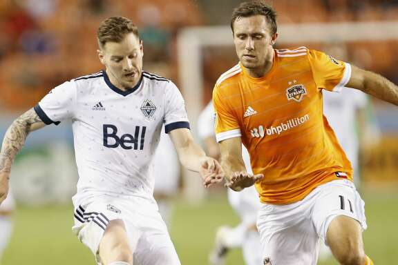 Vancouver Whitecaps defender Jordan Harvey (2) controls the ball pressured by Houston Dynamo forward Andrew Wenger (11) in the second half during the MLS game between the Houston Dynamo and the Vancouver Whitecaps at BBVA Compass Stadium on Friday, May 12, 2017, in Houston, TX.