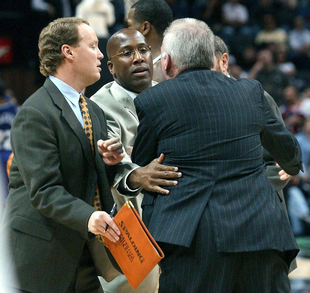 Coach Gregg Popovich (back towards camera) is held back by coaching staff (L-R) Mike Budenholzer, Mike Brown and P.J. Carlesimo, from going towrds the referee that ejected Popovich from the game during the fist half of the game against Sacramento Sunday night, December 8, 2002, at the SBC Center. GLORIA FERNIZ/STAFF