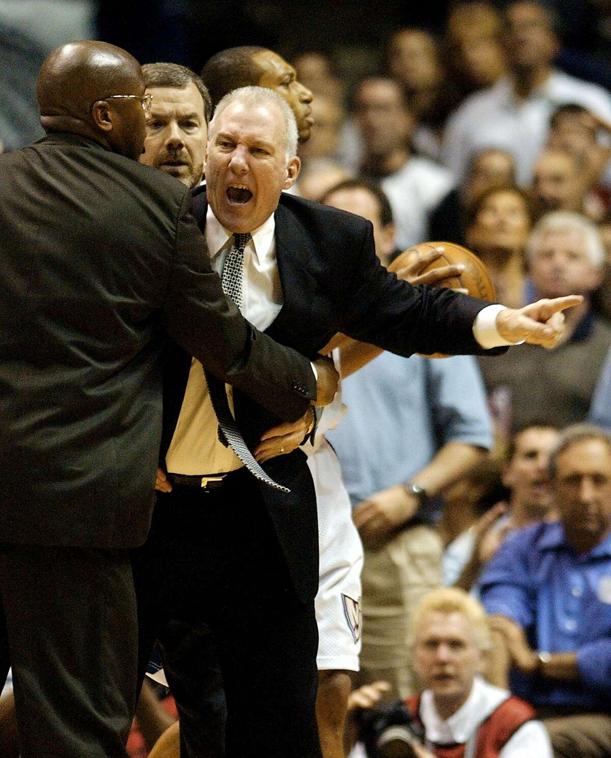 Spurs coach Gregg Popovich is restrained by assistant coach Mike Brown, left and P.J.Carlesimo during third quarter action of game four NBA Finals at the Continental Airlines Arena in New Jersey June 11, 2003. (WILLIAM LUTHER/STAFF)