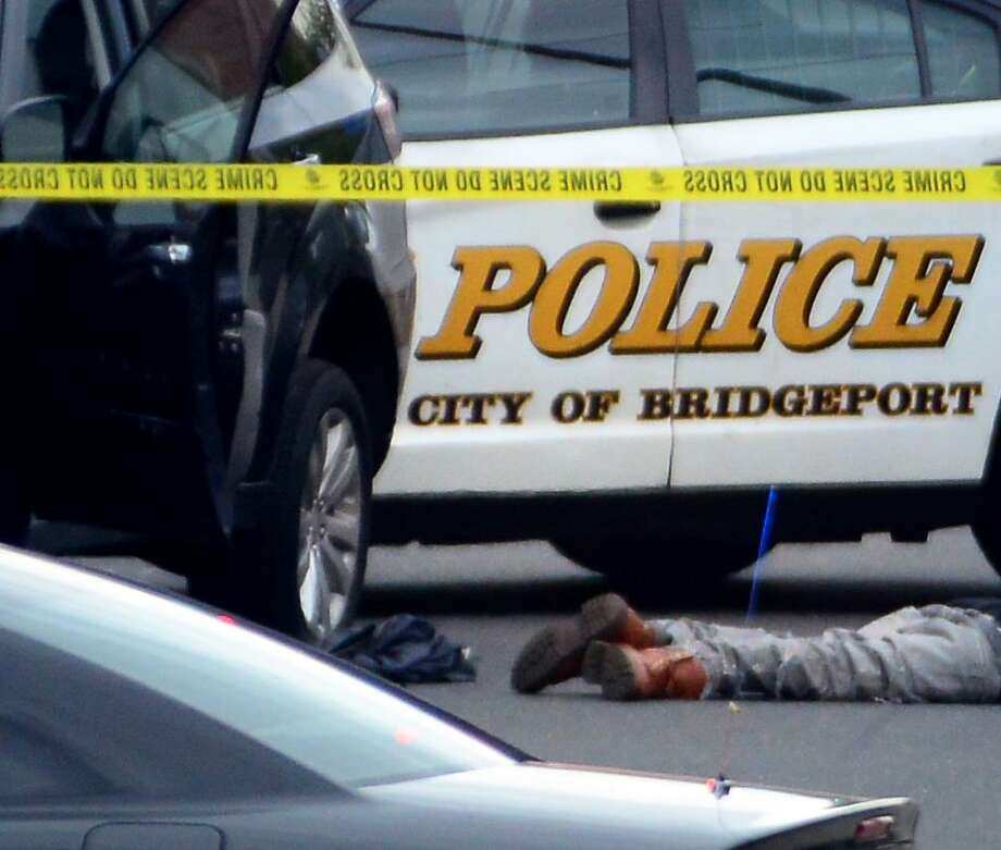 Jayson Negron's body lies on the street after the fatal shooting on Tuesday in Bridgeport. Photo: Christian Abraham / Hearst Connecticut Media / Connecticut Post