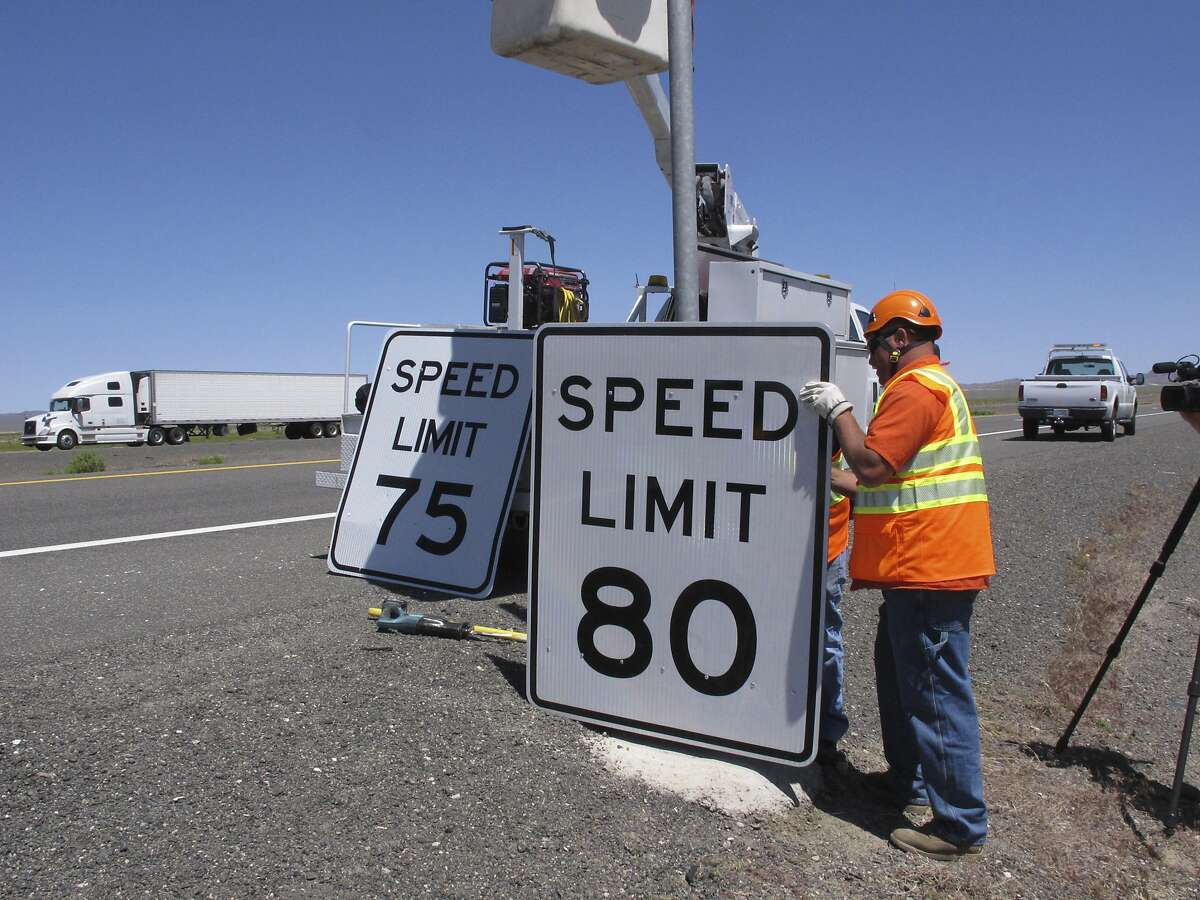Nevada Department of Transportation crews replace a 75 mph speed limit sign with an 80 mph one Monday, May 8, 2017, along U.S. Interstate 80 near Fernley, Nev., about 40 miles east of Reno. Nevada joins South Dakota, Wyoming, Montana, Idaho, Utah and Texas as the only states that now allow speeds in excess of 75 mph on parts of rural highways and interstates. (AP Photo/Scott Sonner)