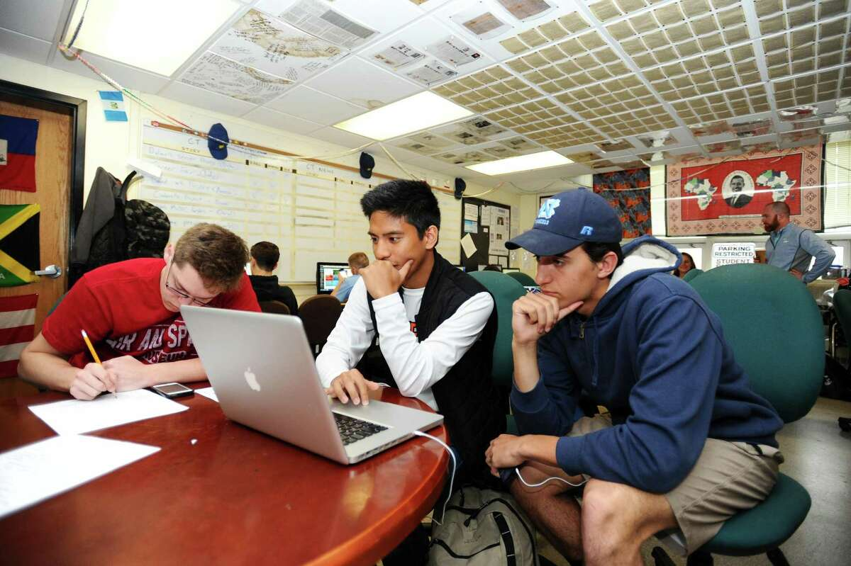 Stamford High School juniors Jude Infante, center, and Joey Price re-watch a video made for the Round Table, Stamford High's student newspaper, during a class inside Stamford High School in Stamford, Conn. on Monday, April 24, 2017.