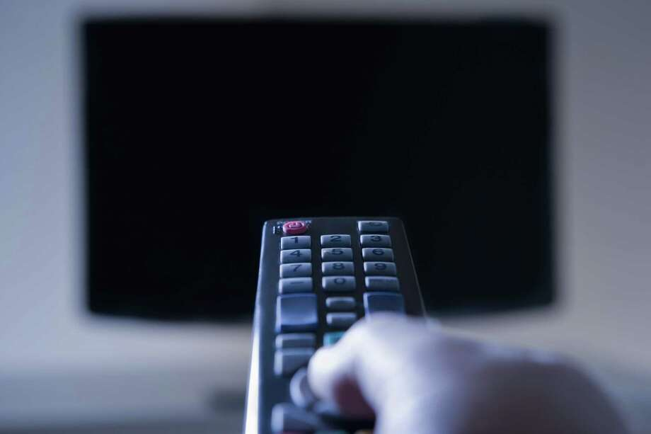 Hispanic man using remote control Photo: REB Images / ONLINE_YES