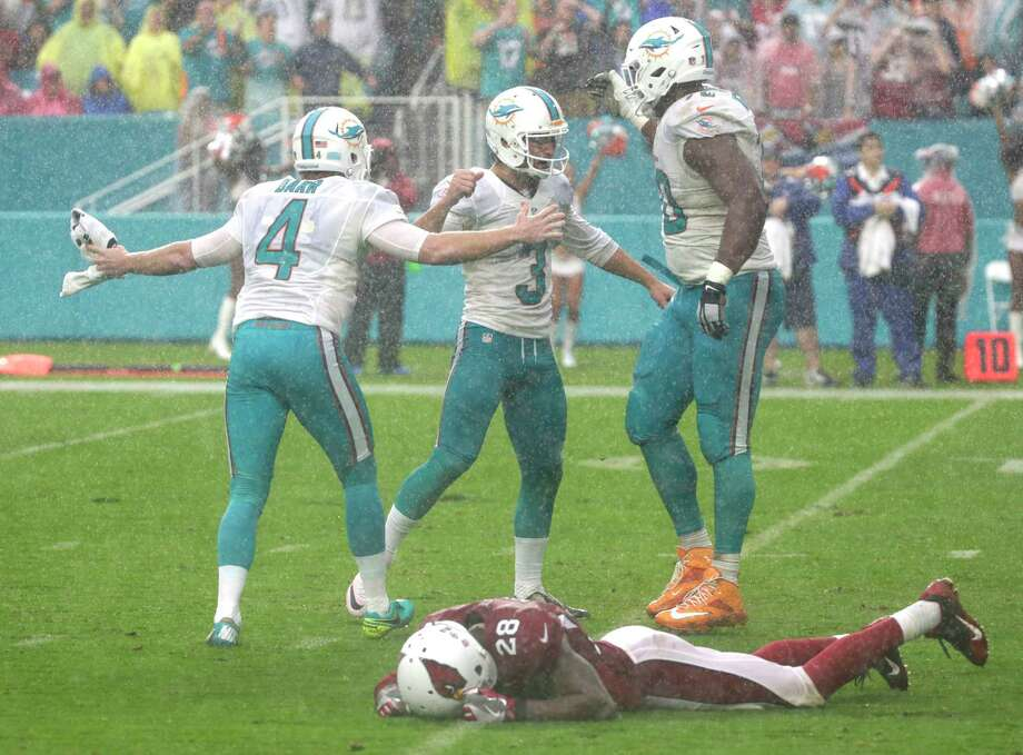 Miami Dolphins tackle Ja'Wuan James (70) and punter Matt Darr (4) congratulate Miami Dolphins kicker Andrew Franks (3, after Franks scored a field goal to win the game, during the second half of an NFL football game, Sunday, Dec. 11, 2016, in Miami Gardens, Fla. To the bottom is Arizona Cardinals cornerback Justin Bethel (28). The Dolphins defeated the Cardinals 26-23. (AP Photo/Wilfredo Lee) ORG XMIT: HRS121 Photo: Wilfredo Lee / Copyright 2016 The Associated Press. All rights reserved.