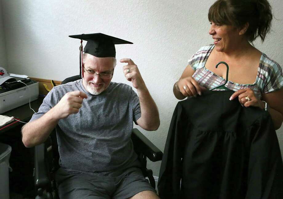 Roni Cornutt helps her husband, Troy, a Navy veteran, try on the cap he will be wearing as he is graduating this weekend after taking mostly online courses at UIW. He suffers from ALS but pursued his degree despite his physical limitations. Roni is a Navy veteran also. Photo: Bob Owen /San Antonio Express-News / ©2017 San Antonio Express-News