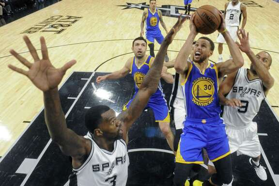 Golden State Warriors' Stephen Curry shoots between San Antonio Spurs' Dewayne Dedmon (left) and Tony Parker during their game Wednesday March 29, 2017 at the AT&T Center. The Warriors won 110-98.
