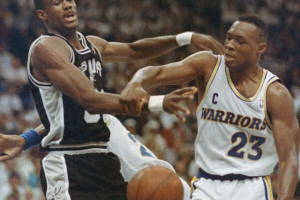 Golden State Warriors Mitch Richmond (23) and San Antonio Spurs David Robinson (50) knock each otherís arms as they go for a rebound during first quarter NBA Playoff Action at the Oakland Coliseum on Friday, May 3, 1991. (AP Photo/Olga Shalygin)