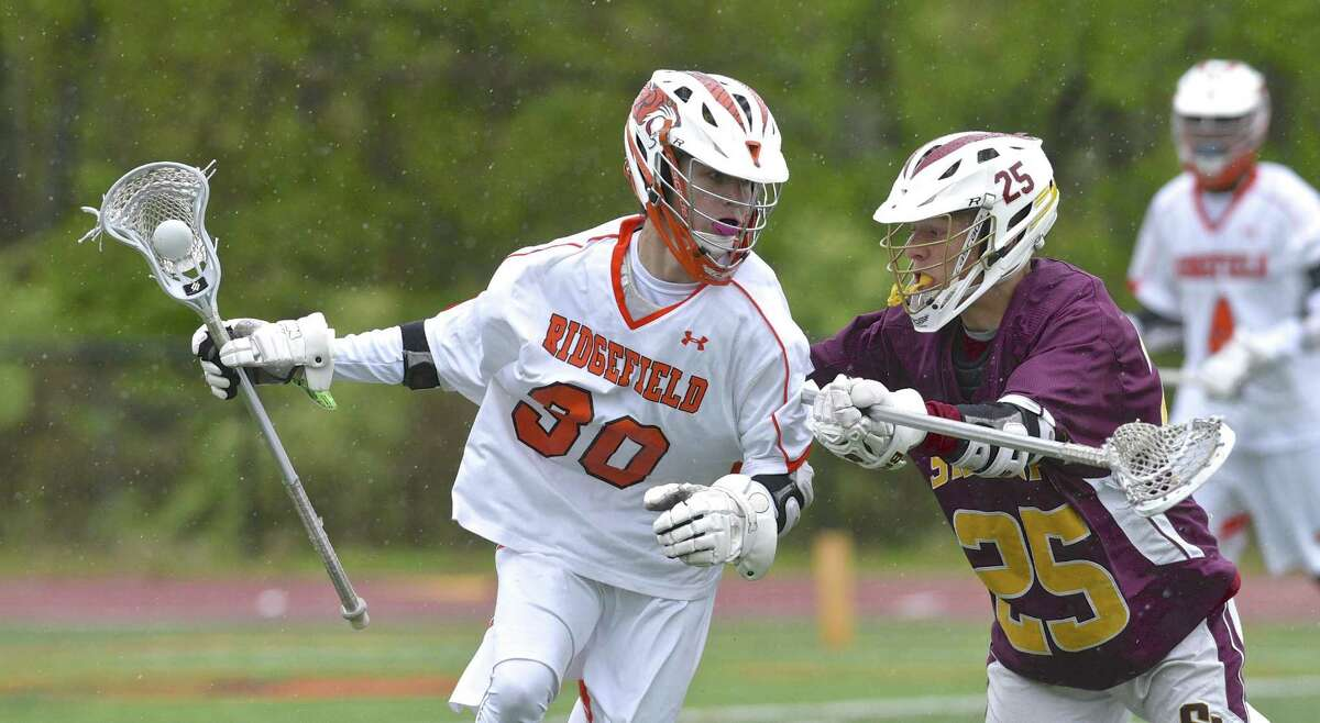 Ridgefield's Harrison Cushmore (30) moves the ball behind the St Joseph goal while being defended by Colin Daly (25) in the boys lacrosse game between St Joseph and Ridgefield high schools, on Saturday afternoon, May 13, 2017, at Ridgefield High School, in Ridgefield, Conn.