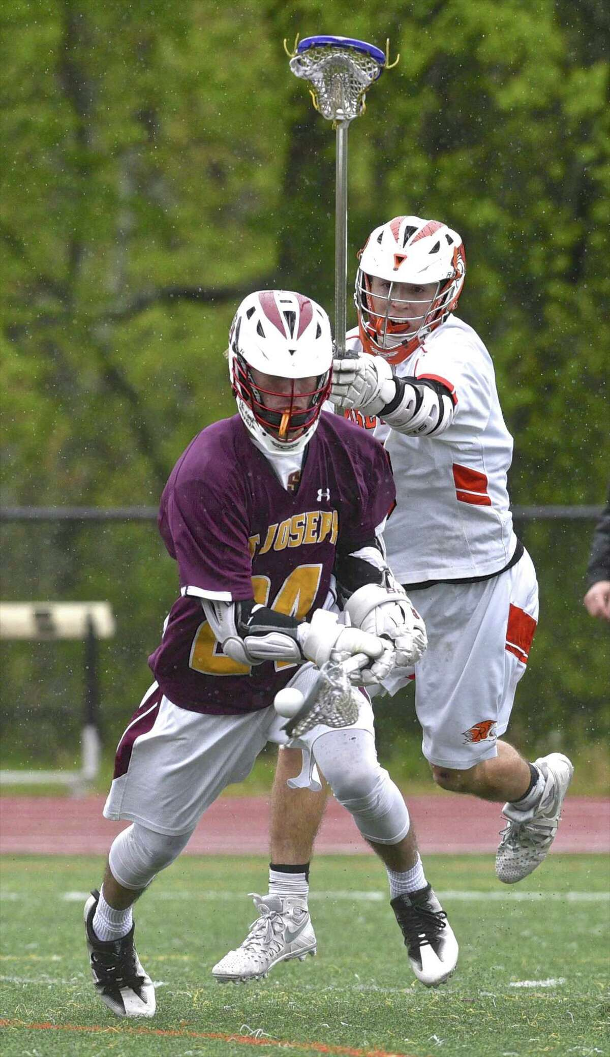 St Joseph's Jared Newel (24) chases the ball while Ridgefield defended Luke Gaydos (10) chases in the boys lacrosse game between St Joseph and Ridgefield high schools, on Saturday afternoon, May 13, 2017, at Ridgefield High School, in Ridgefield, Conn.