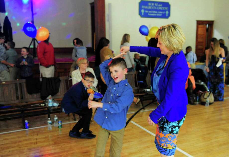 Agnes Kusiak dances with her son Ryan, 8, during Assumption School's 1st Annual Ladies and Little Gents Dance held in the school's newly renovated gym in Ansonia, Conn., on Saturday May 13, 2017. In celebration of Mother's Day, moms as well as grandmas, aunts or other mother figures and sons (up to 8th Grade) came to enjoy the dance. The night included light refreshments and pizza as well as snacks and dessert. A DJ provided music and a souvenir photo station was set up to pose moms with their sons. Photo: Christian Abraham / Hearst Connecticut Media / Connecticut Post