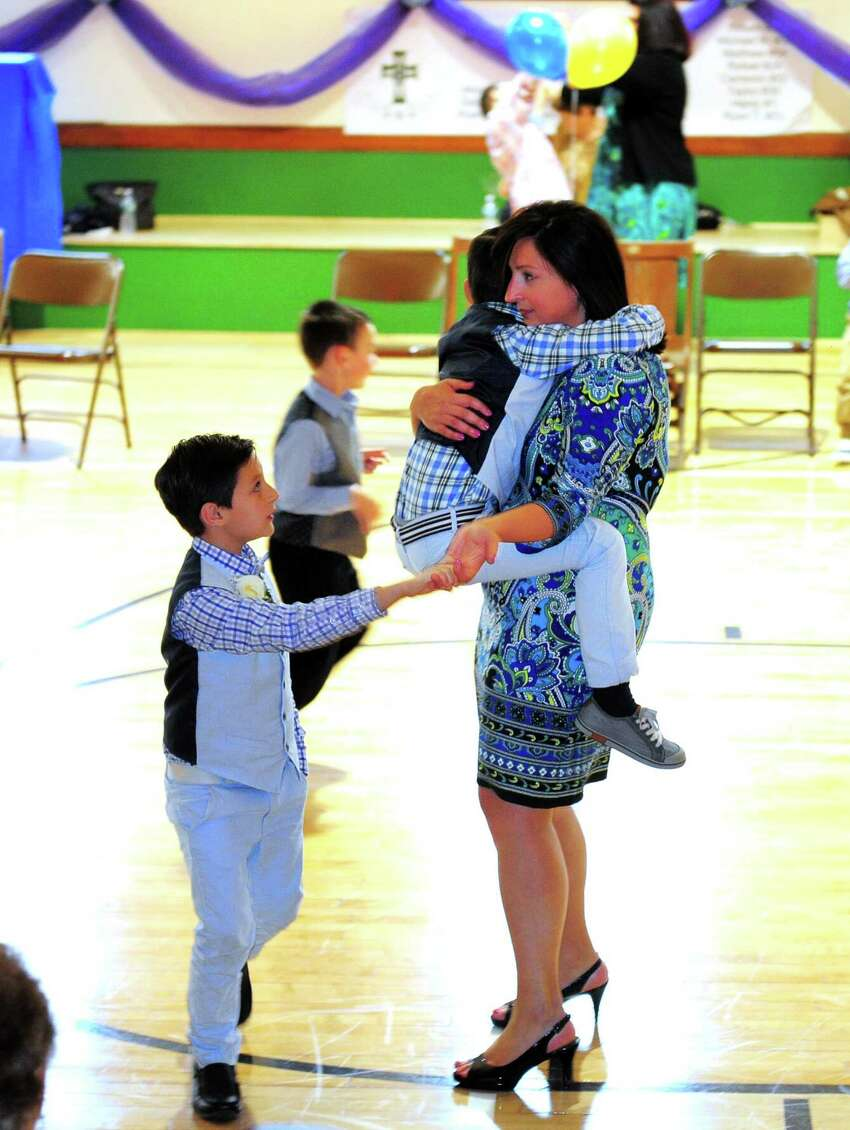 Nancy Marini holds her son Anthony while she dances with her other son Georgie, both 7, during Assumption School's 1st Annual Ladies and Little Gents Dance held in the school's newly renovated gym in Ansonia, Conn., on Saturday May 13, 2017. In celebration of Mother's Day, moms as well as grandmas, aunts or other mother figures and sons (up to 8th Grade) came to enjoy the dance. The night included light refreshments and pizza as well as snacks and dessert. A DJ provided music and a souvenir photo station was set up to pose moms with their sons.