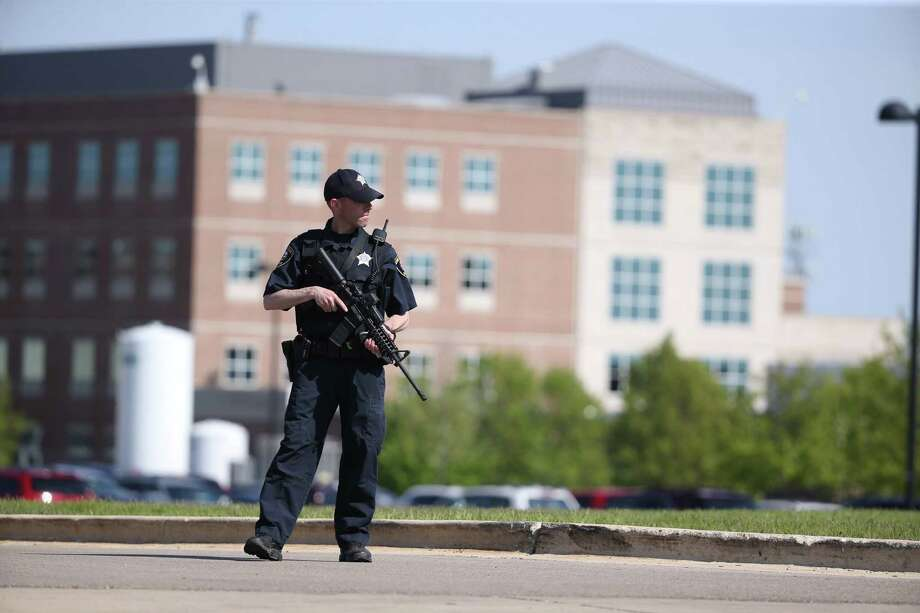 A Kane County police officer monitors the scene at Northwestern Medicine Delnor Hospital in Geneva, Ill., during a lockdown after a jail inmate being treated there managed to take a correctional officer's gun in the facility and hold an employee hostage, Saturday, May 13, 2017. (Chris Sweda/Chicago Tribune via AP) Photo: Chris Sweda, MBO / Chicago Tribune