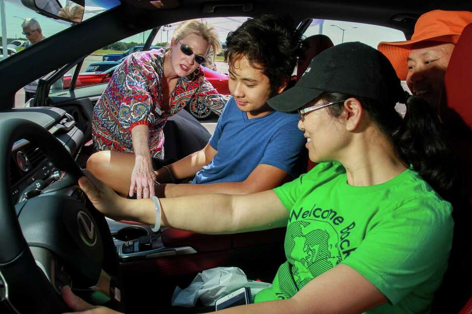 Lisa Gallagher, left, shows Grant Lu and his parents, Susan and Glenn Lu, the voice commands in a Lexus RX350 at a program hosted by Sugar Land that teaches people how to install Bluetooth in their cars. Photo: Gary Fountain, For The Chronicle / Copyright 2017 Gary Fountain