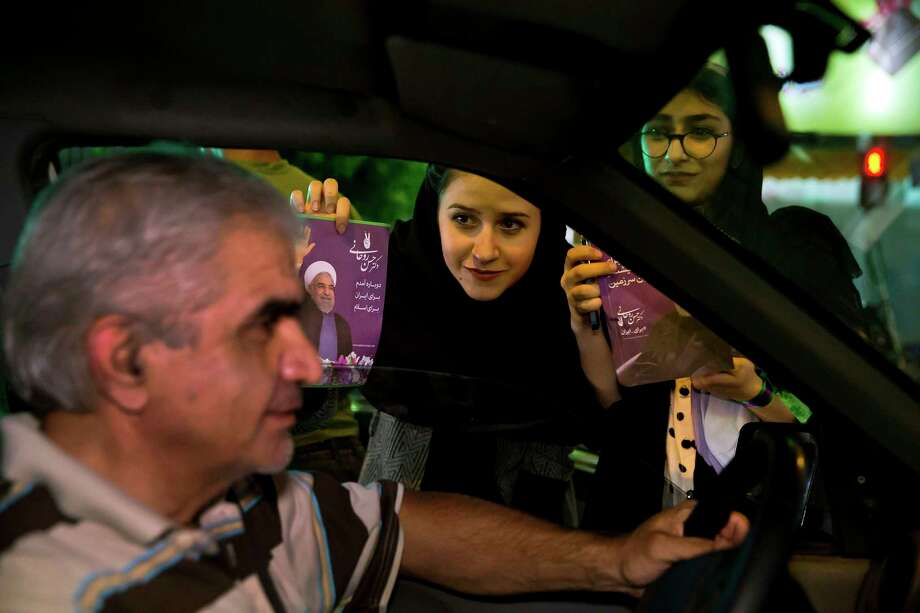 In this Wednesday, May 10, 2017 photo, a supporter of Iranian President Hassan Rouhani hands out his posters for May 19 presidential election in downtown Tehran, Iran. Who wins Iran's upcoming presidential election likely will turn on turnout. Historically, the more Iranians who cast ballots, the greater the chance a reformist or a moderate like incumbent President Hassan Rouhani will be elected. (AP Photo/Ebrahim Noroozi) Photo: Ebrahim Noroozi, STR / Copyright 2017 The Associated Press. All rights reserved.