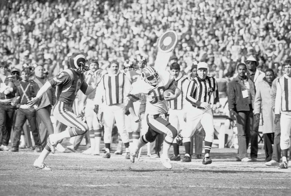 Washinton running bacl Nick Giaquinto (30) attempts to elude Los Angeles Rams punter John Misko (6) on a runback during a game on Jan. 2, 1983.