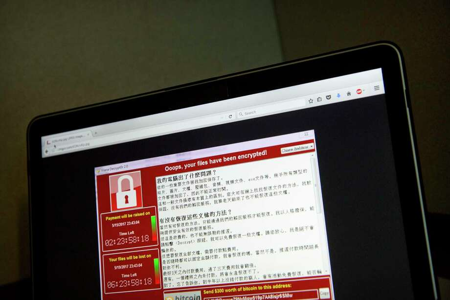 A screenshot of the warning screen from a purported ransomware attack, as captured by a computer user in Taiwan, is seen on laptop in Beijing, Saturday, May 13, 2017. Dozens of countries were hit with a huge cyberextortion attack Friday that locked up computers and held users' files for ransom at a multitude of hospitals, companies and government agencies. (AP Photo/Mark Schiefelbein) Photo: Mark Schiefelbein, STF / Copyright 2017 The Associated Press. All rights reserved.