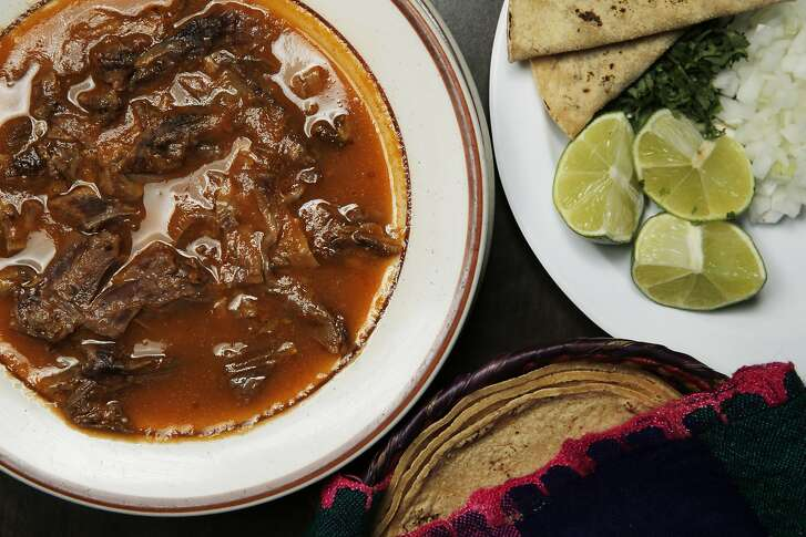Counterclockwise: A bowl of Birria with a plate of lemons, onions, cilantro and bean tacos and a basket of tortillas at El Potrillo restaurant on Saturday, May 13, 2017, in Oakland, Calif. Birria is a Mexican spicy stew traditionally made from goat meat. The restaurant is located at 400 29th Ave.