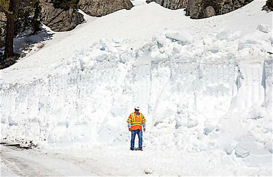 A snow plow crew member stands aside a giant snow drift on Tioga Road/Highway 120, which runs from Crane Flat to Tuolumne Meadows over Tioga Pass in Yosemite National Park Photo: Tom Stienstra, Caltrans