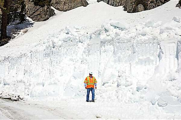 A snow plow crew member stands aside a giant snow drift on Tioga Road/Highway 120, which runs from Crane Flat to Tuolumne Meadows over Tioga Pass in Yosemite National Park