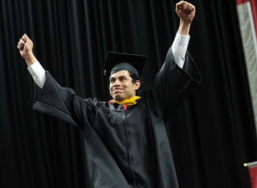 Graduate Andres Morales-Guzman celebrates as he walks across the stage to receive his diploma during Sacred Heart University's 2017 Commencement ceremony.