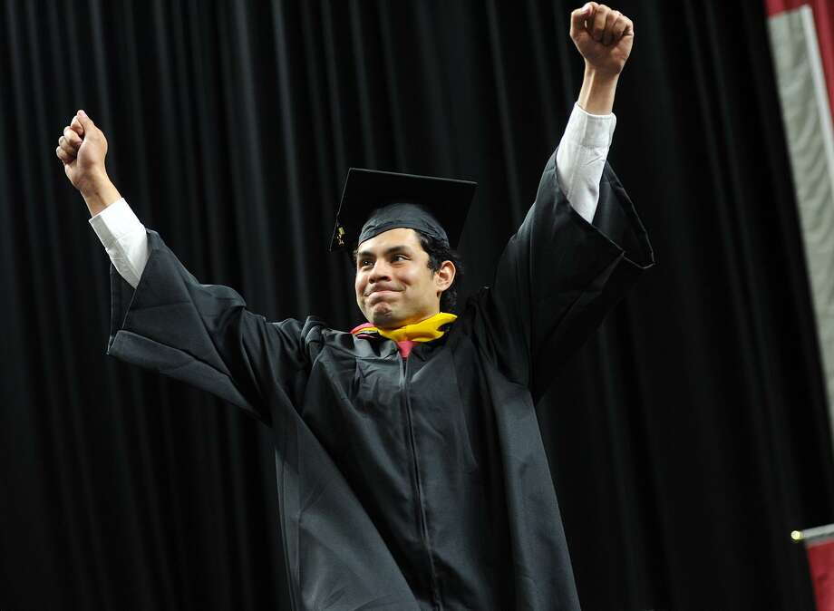 Graduate Andres Morales-Guzman celebrates as he walks across the stage to receive his diploma during Sacred Heart University's 2017 Commencement ceremony. Photo: Brian A. Pounds / Hearst Connecticut Media / Connecticut Post