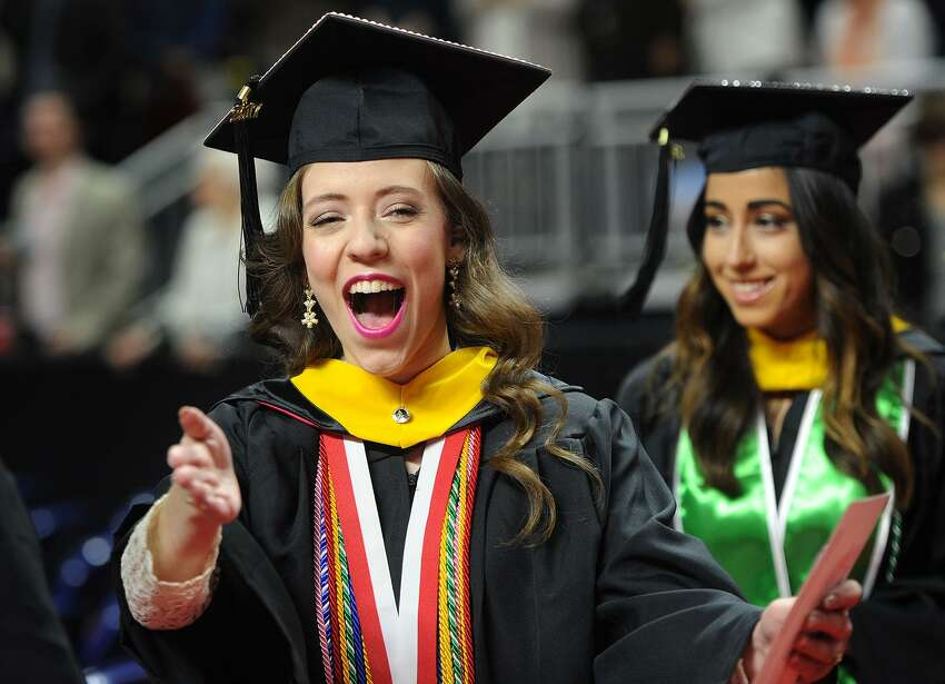 Graduate Lauren Lichac, of Orange, greets a friend with a big smile as she marches in to Sacred Heart University's 2017 Commencement ceremony at the Webster Bank Arena in Bridgeport, Conn. on Sunday, May 14, 2017.