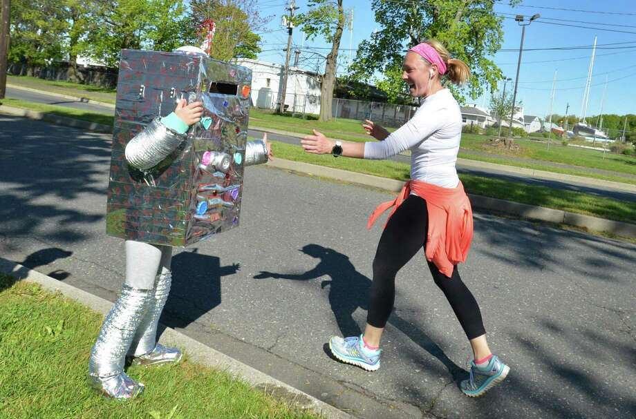 Emma Blank, 7, from Norwalk, cheers her mom Melissa on and gets a high-five for wearing her robot costume as she gets to the finish line during the Lightfoot Running Club & Norwalk Recreation and Parks Mother's Day 10K Race and 5K Health Walk on Sunday, May 14, 2017 in Norwalk. Proceeds from the race benefit the American Heart Association in memory of Norwalk police Capt. Edward T. Donellan. Photo: Alex Von Kleydorff / Hearst Connecticut Media / Norwalk Hour