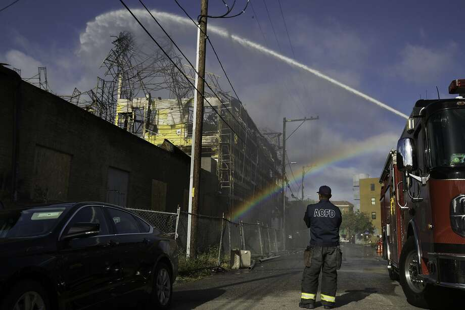 R. Gordon of the Alameda County Fire Department watch es water stream into the complex in May. Photo: Paul Kuroda, Special To The Chronicle