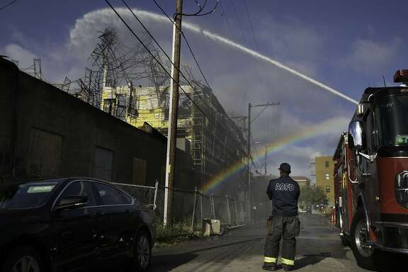 Alameda Fire Dept. Engineer R. Gordon watches 600 gallons per minute stream into a smoking condo complex that was on fire a day before in on Sunday, May 14, 2017 in Oakland, Calif.