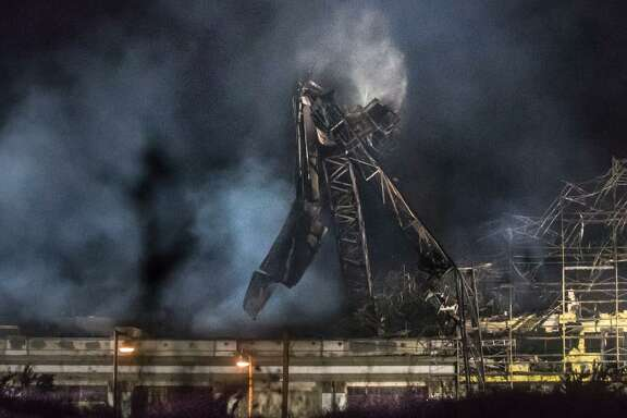 """A severely damage 120-foot crane falls Sunday in Emeryville after a major fire at a building under construction. """"The crane fell exactly as we hoped,"""" said Simon Asselin, director of operations for Bigge Crane and Rigging."""