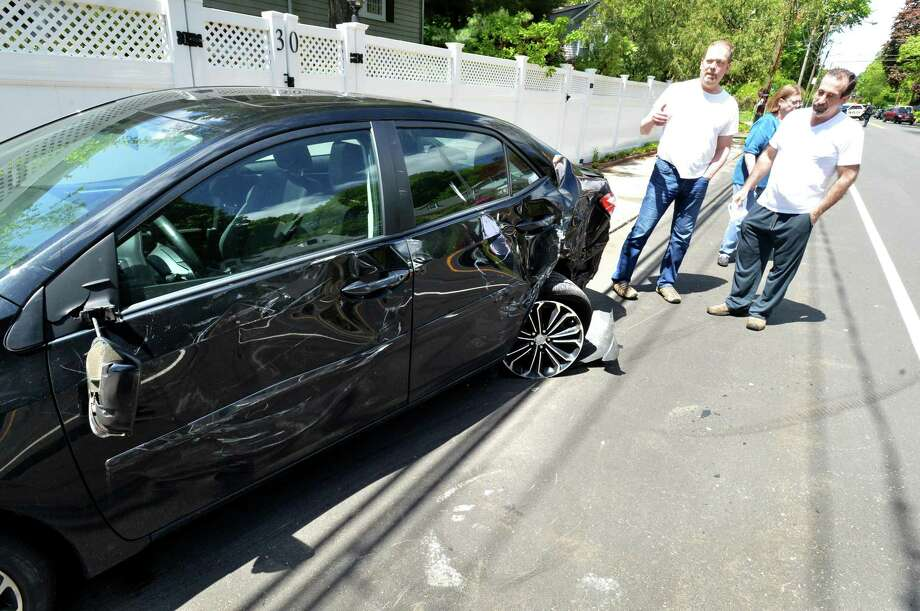 A Toyota Corolla sits pushed onto the sidewalk as the owner and friends look at the driver side damage caused by a motorist in a Subaru that crashed into it and then rolled onto its side on East Avenue in Norwalk on Sunday afternoon. Photo: Alex Von Kleydorff / Hearst Connecticut Media / Norwalk Hour