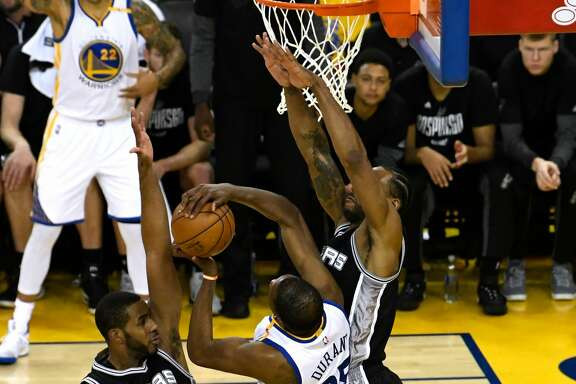 OAKLAND, CA - MAY 14:  Kevin Durant #35 of the Golden State Warriors attempts a shot against Kawhi Leonard #2 and LaMarcus Aldridge #12 of the San Antonio Spurs during Game One of the NBA Western Conference Finals at ORACLE Arena on May 14, 2017 in Oakland, California. NOTE TO USER: User expressly acknowledges and agrees that, by downloading and or using this photograph, User is consenting to the terms and conditions of the Getty Images License Agreement.  (Photo by Thearon W. Henderson/Getty Images)