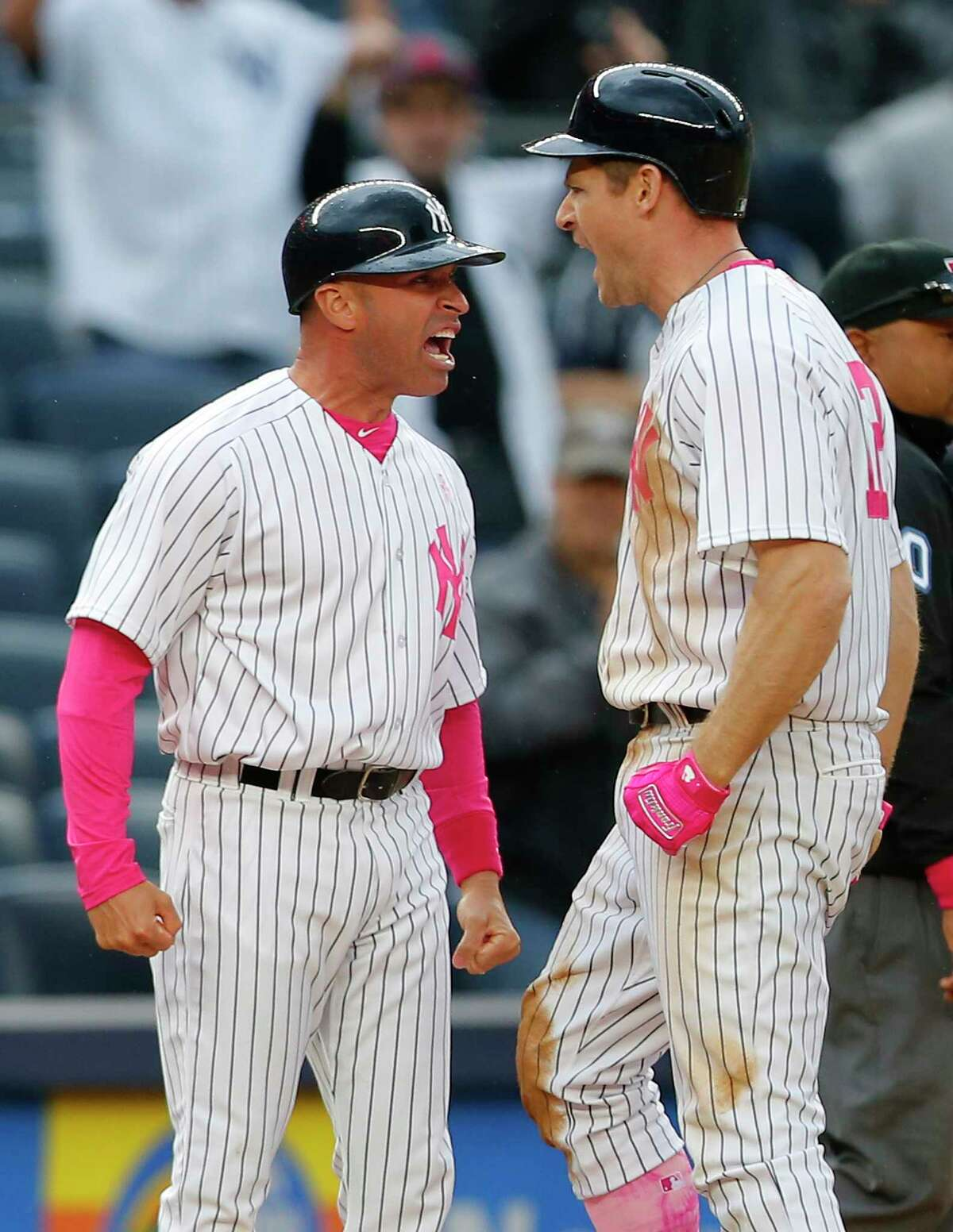 NEW YORK, NY - MAY 14: Chase Headley #12 of the New York Yankees reacts with third base coach Joe Espada #53 after he hit a bases loaded triple during the seventh inning against the Houston Astros during game one of a doubleheader at Yankee Stadium on May 14, 2017 in New York City. Players are wearing pink to celebrate Mother's Day weekend and support breast cancer awareness.