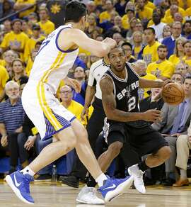 San Antonio Spurs' Kawhi Leonard looks for room against Golden State Warriors' Zaza Pachulia during second half action of Game 1 in the Western Conference Finals held Sunday May 14, 2017 at Oracle Arena in Oakland, CA. Leonard was injured on a play. The Warriors won 113-111.