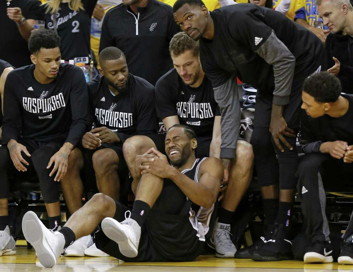 San Antonio Spurs' Kawhi Leonard reacts after being injured on a play as teammates Dejounte Murray (from left), Jonathon Simmons, David Lee, Dewayne Dedmon and Bryn Forbes look on during second half action of Game 1 in the Western Conference Finals against the Golden State Warriors held Sunday May 14, 2017 at Oracle Arena in Oakland, CA. The Warriors won 113-111.