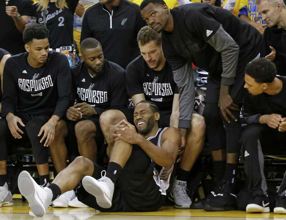 San Antonio Spurs' Kawhi Leonard reacts after being injured on a play as teammates Dejounte Murray (from left),  Jonathon Simmons, David Lee, Dewayne Dedmon and Bryn Forbes look on during second half action of Game 1 in the Western Conference Finals against the Golden State Warriors held Sunday May 14, 2017 at Oracle Arena in Oakland, CA. The Warriors won 113-111. Photo: Edward A. Ornelas,  Staff / San Antonio Express-News / © 2017 San Antonio Express-News