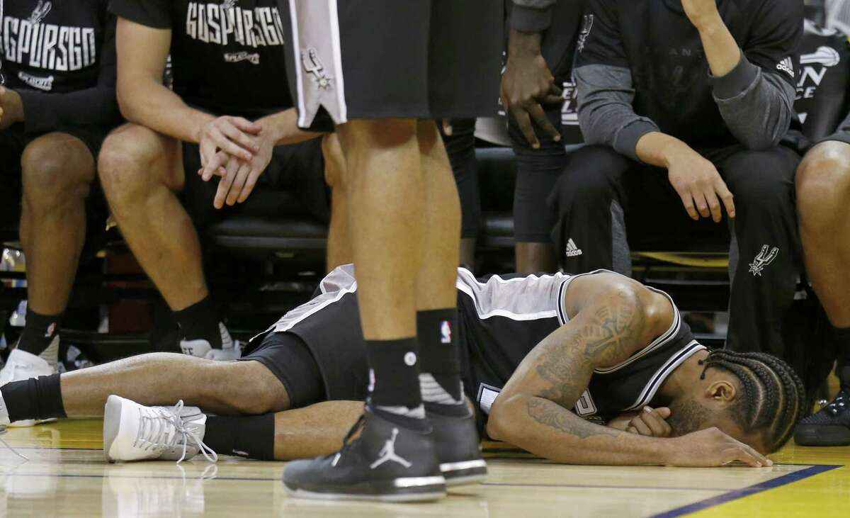 Spurs' Kawhi Leonard reacts after being injured on a play during second half action of Game 1 in the Western Conference finals against the Golden State Warriors on May 14, 2017 at Oracle Arena in Oakland, Calif.