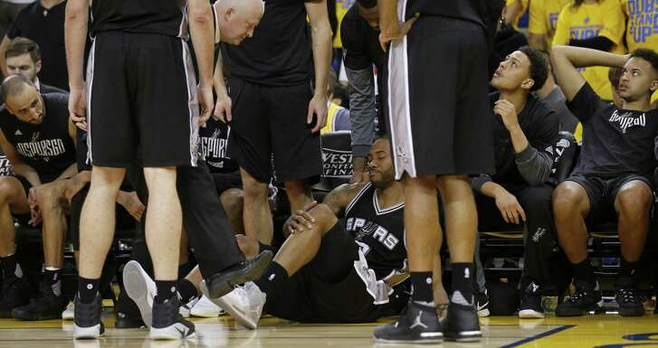 Spurs' Kawhi Leonard (center) reacts after being injured on a play as head trainer Will Sevening (left) looks on during second half action of Game 1 in the Western Conference finals against the Golden State Warriors on May 14, 2017 at Oracle Arena in Oakland, Calif.