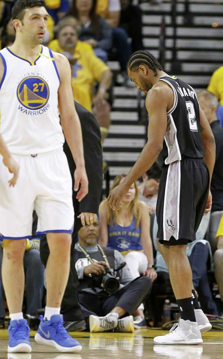 Spurs' Kawhi Leonard walks off the court after being injured on a play involving the Warriors' Zaza Pachulia(left) during second half action of Game 1 in the Western Conference finals on May 14, 2017 at Oracle Arena in Oakland, Calif.