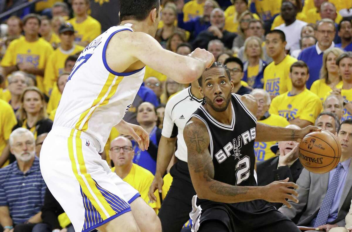Spurs' Kawhi Leonard looks for room against Golden State Warriors' Zaza Pachulia during second half action of Game 1 in the Western Conference Finals. Leonard was injured on the play and the Warriors won 113-111. Click through to see how fans reacted to the seemingly